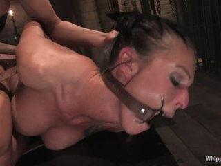 Tied up and gagged slut gets fucked in the ass with a dildo by another whore.