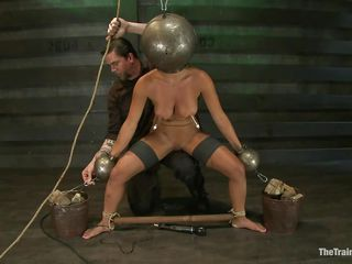 Adrianna Luna has her legs held apart by a support and her hands are encased by metal balls. Her head is encased by a metal ball as well and pumps on her nipples. She gets a vibrator on her cunt and gets the ok to cum. Then she's tied to a table and having clamps put on her pussy and tits. Freaky!