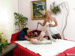 After masturbating for a while the brunette mature gets fingered by a granny until she is moaning with pleasure. Then the granny inserts a vibrator in her shaved pussy between those sexy spread legs. She wears a pair of white stockings and high heels that only makes her mature body hotter.