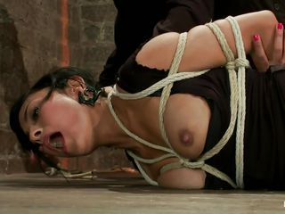Berreta James is a brunette milf with big tits who likes being hogtied. Watch her as she stands immobilized on the floor with her leg hanging up. Hear her moaning and screaming with immense pleasure as a man in a tuxedo comes and starts arousing her, moving a vibrator over her clitoris and her shaved pussy.