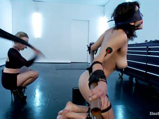 Watch this hot babe Raven Rockette with big tits being punished for all her sins. Her body is tied up into a bondage device and she has electrodes on her triceps and a ball gag on her mouth. Gorgeous blonde domina Aiden Starr is there to enhance the pleasure, using a long electric wand that she has.