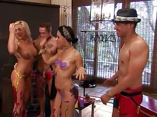 they were standing there chatting away and having a couple of nice relaxing drinks when the mistress of ceremonies entered and all hell broke loose. She made them horny and they removed their clothes in no time. Stick around and see how these sex games will continue, there's a lot to watch.