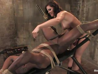 Jack Hammerx is getting harmed in his anus by this dominant milf. She likes to fuck muscled guys in his anus with her strap on dildo and does t in her own rhythm without hurrying. The black guy is tied on that bondage table that keeps his legs wide open so she could have full access to his anus.
